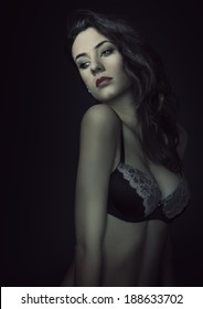 young beautiful sexy girl wearing a fashion bra , and posing on dark background. she has hairstyle looking down