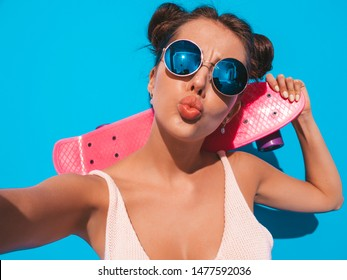 Young beautiful sexy smiling hipster woman in sunglasses.Trendy girl in summer knitted cardigan.Female with pink penny skateboard,isolated on blue wall.Taking selfie self portrait photos on phone