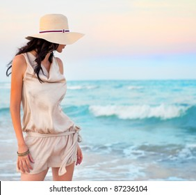 Young beautiful sexy tanned brunette woman wearing straw hat and elegant dress posing standing on beach near waves and looking away at the sea
