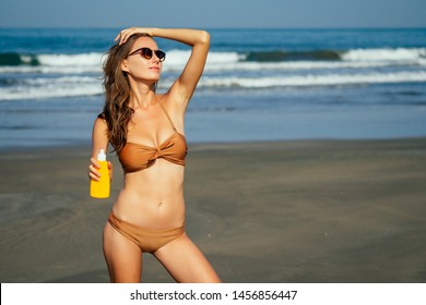 Young beautiful sexy tanned happy fitness woman in fashion style bikini during sunbath on sea beach summer .slender girl depilation hair removal shugaring