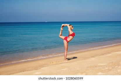 The young, beautiful, sexy woman in a bathing suit trains yoga on the tropical beach