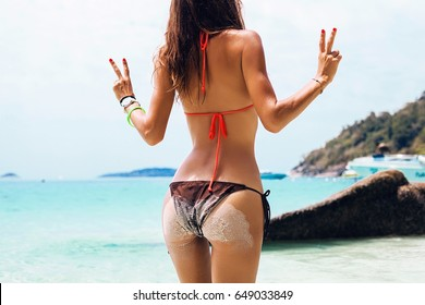 young beautiful sexy woman in bikini swimsuit, tropical island, summer vacation, resort fashion style, sand, slim, tanned, beach, view from back, booty, showing peace sign, positive mood, happy, hips