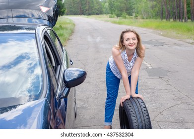 Young beautiful sexy woman at broken car with mobile phone, standing in the public road in forest area, calling for help with mobile phone. Broken vehicle in the background.