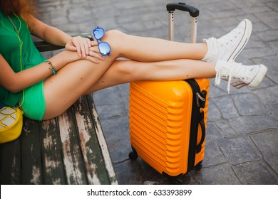 young beautiful sexy woman, hipster outfit, traveler, green shorts, top, orange suitcase, sneakers, sitting, waiting, summer vacation, colorful, traveling around world, legs details close up