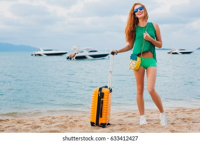 young beautiful sexy woman, hipster style, red hair, traveler, green outfit, orange suitcase, tropical beach, summer vacation, traveling around world, adventure, colorful, happy, positive, smiling