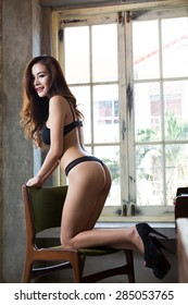 Young beautiful sexy woman lin lingerie posing in vintage style room