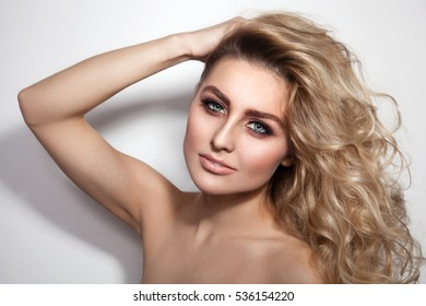 Young beautiful sexy woman with long curly hair and stylish make-up