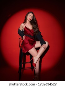 Young beautiful sexy woman with make-up and wavy brunette hair in red silk dress posing against red background in circle of light (spot gobo light)