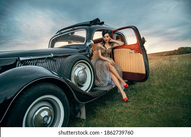 Young beautiful sexy woman in pin-up style clothes sits posing in black retro car. Polka dot white dress, vintage hairstyle, red high heels. Background road nature summer. Girl fashion model driver.
