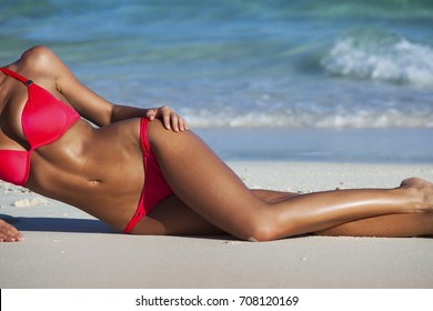 Young beautiful sexy woman relaxing on the beach