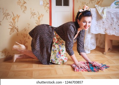 Young beautiful sexy woman washes the floor. Shooting in pinup style, retro.
