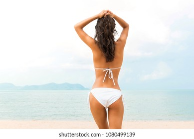 Young beautiful shape tan skin woman wearing white bikini swimsuit posing at the beach in summer, back view
