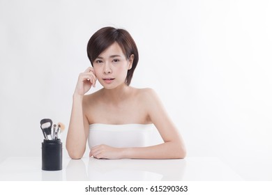 Young beautiful short hair Asian girl with face brush pouch on the isolated white background