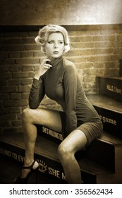 Young beautiful short hair blonde woman in turtle neck tight short dress sitting on stairs, black and white photo. Romantic mysterious lady with movie star retro look posing, bricks wall background.