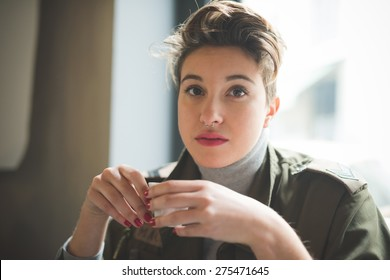 young beautiful short hair hipster woman at the bar drinking coffee