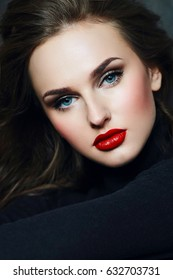 Young beautiful showy girl with luxurious wavy shiny hair looks into the frame. Brown-haired, blue eyes, big red lips. A large portrait. Fashion, beauty, care, health. Salon.