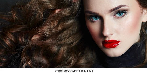 Young beautiful showy girl with luxurious wavy shiny hair looks into the frame. Brown-haired, blue eyes, big red lips. A large portrait. Fashion, beauty, care, health. Salon.Beautiful long hair.