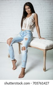 Young beautiful showy girl with luxurious, shiny hair sitting on a bar stool. Brown hair, blue eyes, big lips. Blue ragged jeans. Fashion, beauty. Salon.
