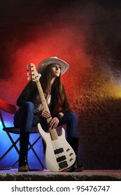 Young beautiful young singer is sitting on stage with a bass guitar