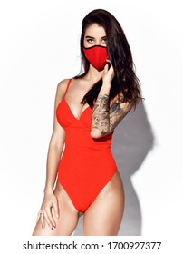 Young beautiful slim brunette woman with tattooed arm in sexy orange swimsuit wearing red mask for protection from coronavirus over white background. Stylish virus protection concept