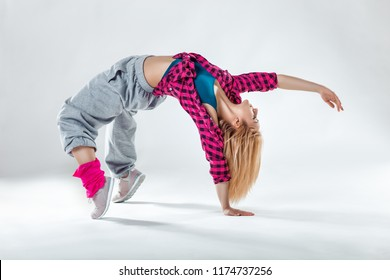 Young beautiful slim girl dancing on a white studio background