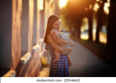 A young beautiful slim woman in a blue dress with her little cute baby walking around the old town on a sunny summer day.
