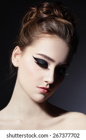 Young beautiful slim woman with fancy cat eye make-up and stylish hairdo