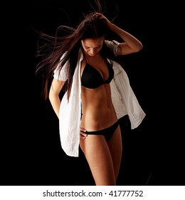 Young beautiful slim woman posing in bikini - with wind - isolated on black