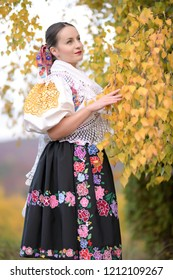 Young beautiful slovak woman in traditional costume on autumn nature.