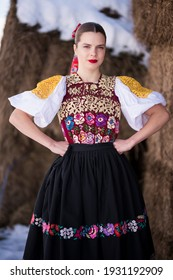Young beautiful slovak woman in traditional dress in winter. Slovak folklore