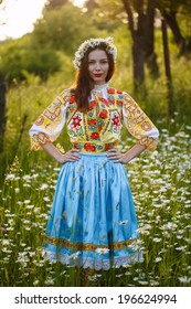 Young beautiful slovak woman in traditional costume on summer daisy meadow during sunsent