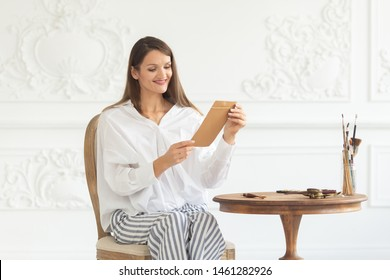 A young beautiful smailing girl in a luxurious interior sits on a chair holding a love letter from her boyfriend and reads it. Romantic mood on Valentine's Day. Soft focus.