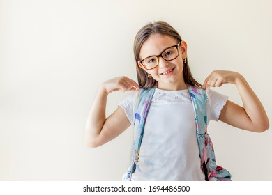 Young beautiful smart student girl wearing backpack over isolated background looking confident with smile on face, pointing oneself with fingers proud and happy