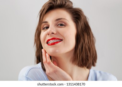 Young beautiful smiley woman with braces and bright makeup