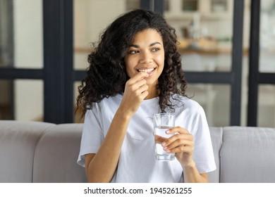 Junge schöne lächelnde afrikanische Amerikanerin, die eine Vitamin-Pille und ein Glas Wasser hält, sitzen auf dem Sofa zu Hause. Gesunder Lebensstil, gesunde Ernährung