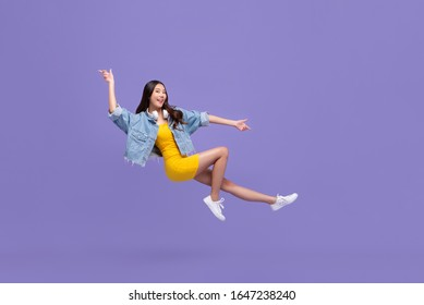 Young beautiful smiling Asian girl floating in mid-air with hand pointing up and down isolated on purple background