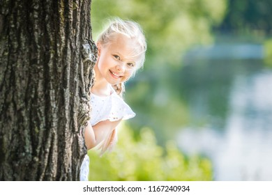 Young beautiful smiling blond girl in a white dress peeping out of a big tree trunk