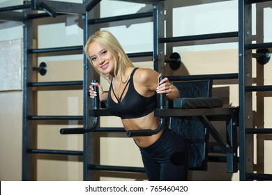 young beautiful smiling blonde girl is exercising in the gym