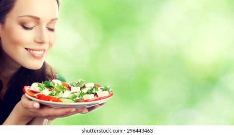Young beautiful smiling brunette woman with plate of salad, outdoor, with blank copyspace area for slogan or text message