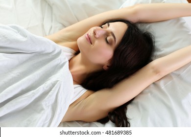 Young beautiful smiling and brunette woman lying in bed trying to wake up early morning stretching hands after sleep. Sweet dreams, good morning, new day, weekend, holidays concept