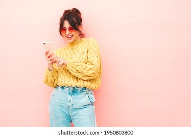 Young beautiful smiling female in trendy summer yellow hipster sweater and jeans.Sexy carefree woman posing near pink wall in studio.Positive model having fun. Looking at smartphone screen, using app - Shutterstock ID 1950803800