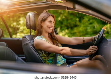 Young beautiful smiling girl driving a car.