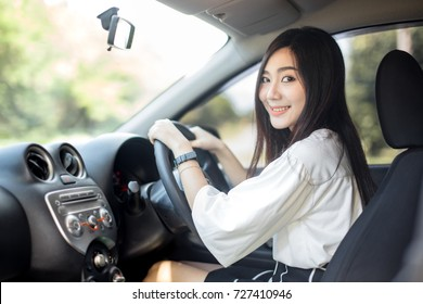 Young beautiful smiling girl driving a car