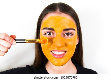 Young beautiful smiling girl with a mask of turmeric on her face on a white background holds a brush. Face Close Up