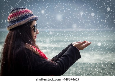 Young beautiful smiling girl showing open hand palm. In the background, a lake and a hill landscape. She is wearing dark sunglasses, black coat, colorful hat and scarf. shallow depth of field