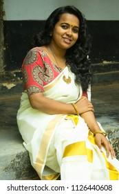 Young beautiful smiling Kerala/Indian girl/woman in traditional set saree, kalamkari blouse and golden bangle