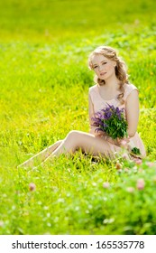 Young beautiful smiling woman in the field, on the grass. Girl resting on the outside.