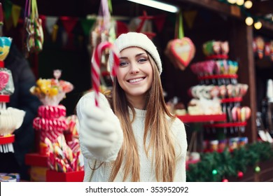 Young beautiful smiling woman holding Christmas candy cane. Festive fair as background. Selective focus on the model. The object is defocused. Close up