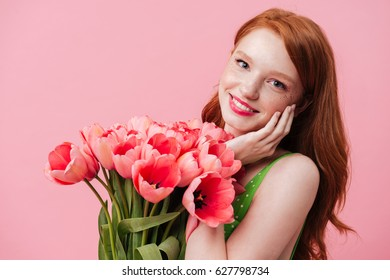 Young beautiful smiling woman holding tulips near face isolated