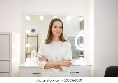 Young beautiful smiling woman joyfully looking in camera over white background. Make up artist by the mirror in her studio
